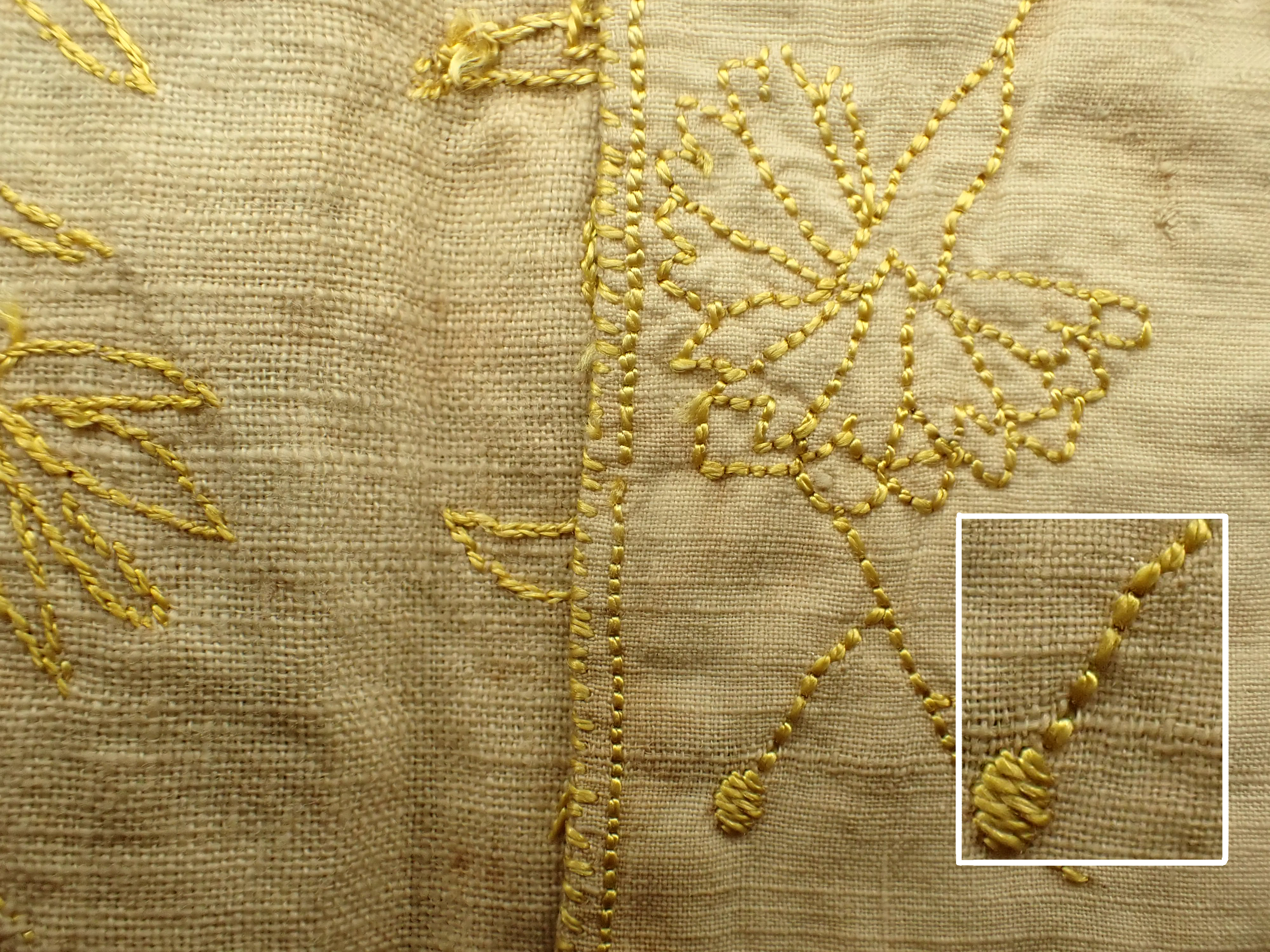 photo to show detail of flower and stitches worked in yellow silk on undyed linen card case with insert at 250x to show that the silk is floss, 2-ply.