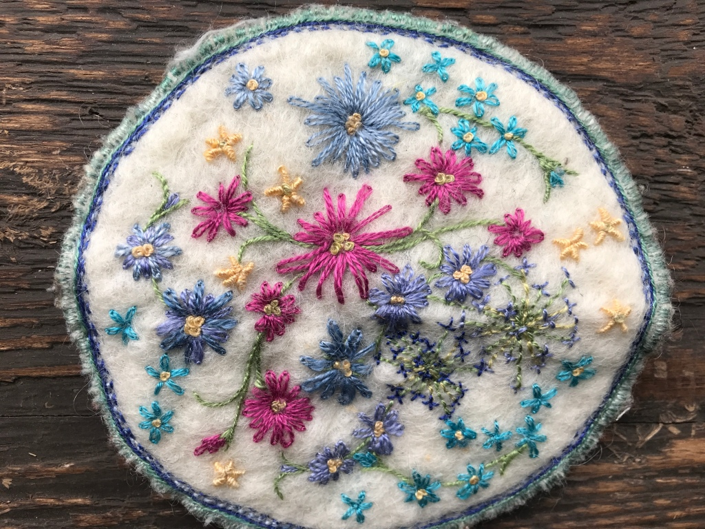 Disk of white felt embroidered with handspun silk flowers using chain stitch, stem stitch, bullion stitch and french knots in pink, blue, cyan, yellow and green.